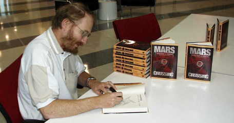 photo of Geoffrey Landis signing books